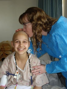 Nurse Cyndi kisses my bald head before my very last hospital chemo.